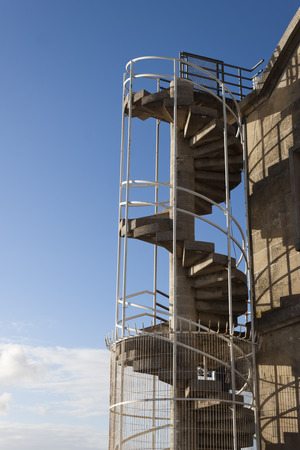 Outdoors spiral staircase in a building with blue sky as