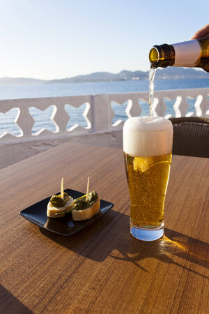 Pouring cold beer from the bottle in a glass and a plate of green peppers in the table of a terrace next to the sea in Spain  photo