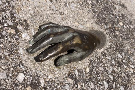 sculpted: Sculpted bronze man hand buried in concrete