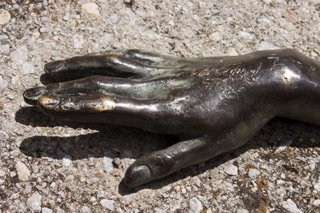 sculpted: Gebeeldhouwde bronzen vrouw hand begraven in beton