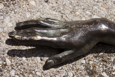sculpted: Sculpted bronze woman hand buried in concrete  Stock Photo