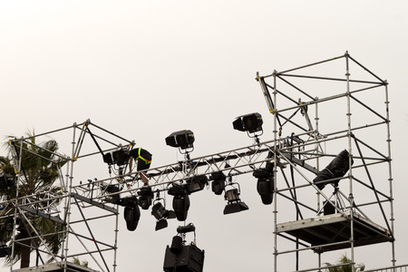 lighting technician: Lighting technician in a stage structure arranging spotlights.