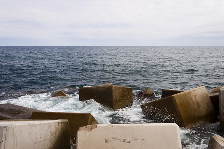 groyne: Breakwater with some concrete cubes in the sea.