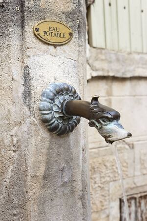 potable: Bronze metal spout in an antique public fountain in Gigondas, vaucluse, France. Stock Photo