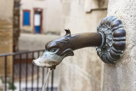 Bronze bec métallique dans une fontaine publique antique à Gigondas, Vaucluse, France.