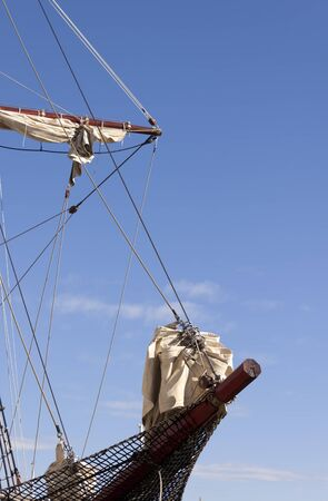 furled: Bowsprit of a sailing ship with furled jibs with clear blue sky as background. Stock Photo