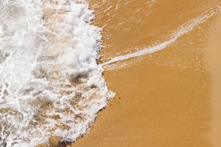 breaking in: White foamy wave breaking in the sand of the beach. Summer background. Stock Photo