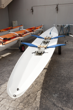 rowing boat: Red two places racing rowing boat with sliding seats. Stock Photo