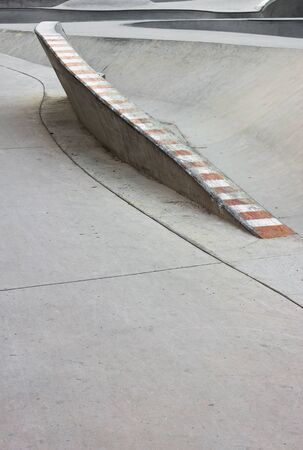 skate park: Rail in an empty concrete skate park.