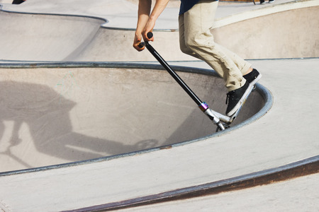 skate park: Boy in a concrete skate park with a push scooter making a trick in the rail of a bowl. Stock Photo