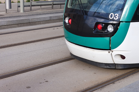 streetcar: Close-up of a modern green and white tram in the rails. Detail of the lights, a number three and the driver cab of the streetcar stopped in the tramway station. Editorial