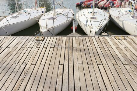dinghies: Four small learning sailing boats in a row in a wooden jetty. Big copy-space for placing text and some red pneumatic dinghies at background. Stock Photo