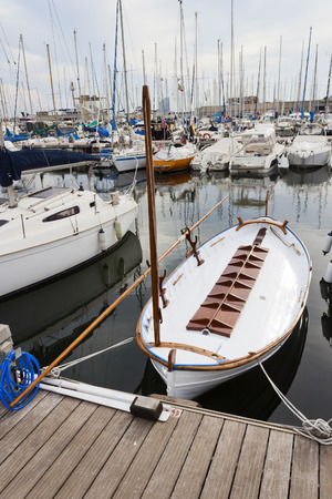 restored: White wooden vintage boat moored in the pier in calm. The yacht is restored and the wood painted and varnished.