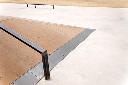 grind: Detail of a wooden jump box with metal rail for grind skate tricks in an empty skate-park. Copy-space for placing text.