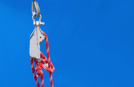 tackle: Nautical knot on red ropes and tackle of a yacht on blue textile background. Big copy-space for placing text.