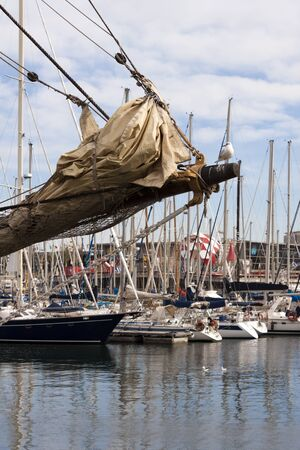 furled: Bowsprit of a sailing ship with furled jibs and seagull  in the harbor with  moored yachts in background.