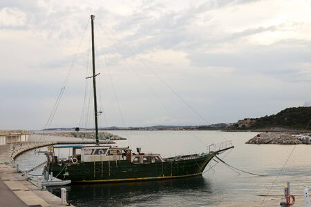 peeling paint: Green wooden vintage vessel moored in the pier in Roc de Sant Gaieta, Tarragona, Spain. The yacht is old and rusty with peeling paint. Stock Photo