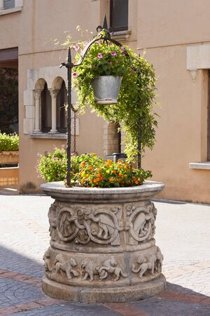 sculpted: Antique sculpted stone water well and bucket with flower plants decorations  in Roc de Sant Gaieta, Tarragona, Spain. Stock Photo