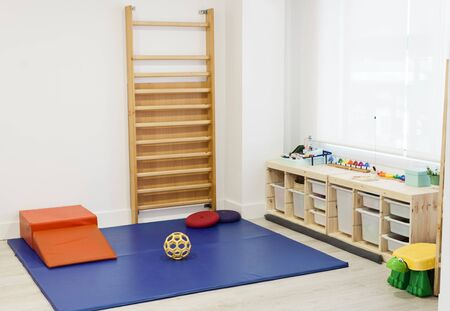 Empty physiotherapy clinic with pad and equipment for kids rehabilitation