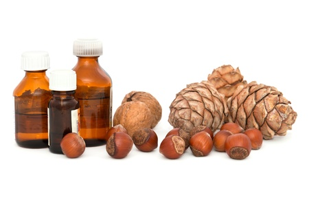 Walnuts, hazelnuts and pine nuts  Bottles with different oils  photo