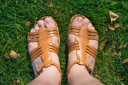 The photo shows the legs in sandals on a green grass. View from above.