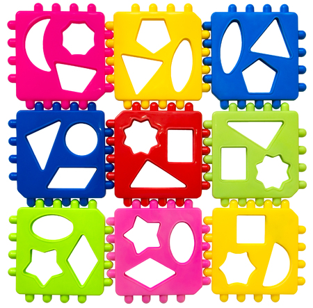 Multicolored plastic puzzles on a white background. View from above. Early development of children. The study of geometric shapes. Stock Photo