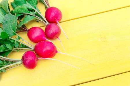 Five radishes with tops lie on a wooden table. The photo is made at an angle. Reklamní fotografie