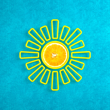 Creative sun with a kernel in the form of an orange. Bright turquoise background. Illustration in the style of minimalism. 3d illustration. Stock Photo