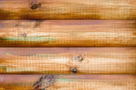 Wall of a log house. Log-house. Wall of painted logs. Wood background. The logs are painted with colorful stains. Фото со стока