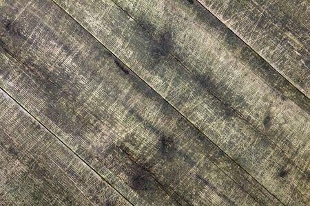 Old badly scratched boards. Wood background. Grunge style. Floor with scuffs. Diagonal.