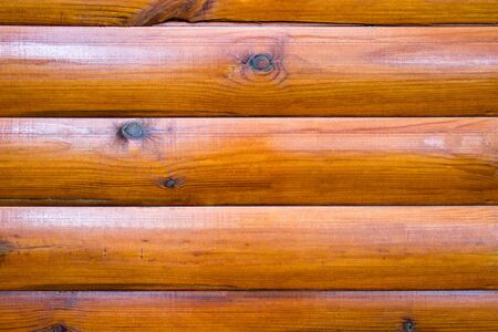 Wall of a log house. Log-house. Wall of painted brown logs. Wood background. Country style.