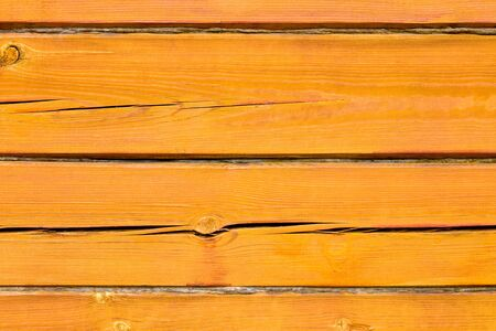 Wall of a log house. Log-house. Wall of painted orange logs. Square beam. Wood background. Country style.