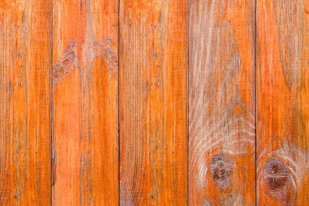 Old wooden boards with peeling paint. Wooden fence. Grunge style. Orange paint. Old decoration. Stock Photo