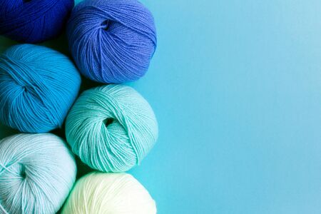 Acrylic balls of yarn on a blue background. Nuance color combination. Skeins are located vertically on the left.