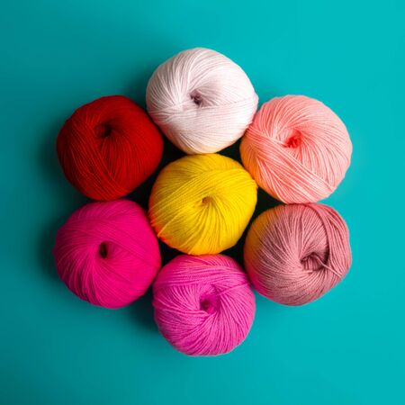 Acrylic balls of yarn on a blue background in the shape of a flower. Nuance color combination. The balls are arranged in a circle.