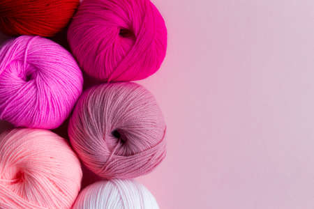 Acrylic balls of yarn on a pink background. Nuance color combination. Skeins are located vertically on the left. Archivio Fotografico