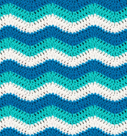 Seamless knitted texture. The pattern in the form of waves crocheted with multi-colored threads. Acrylic baby yarn. Sea style. Colorful background.