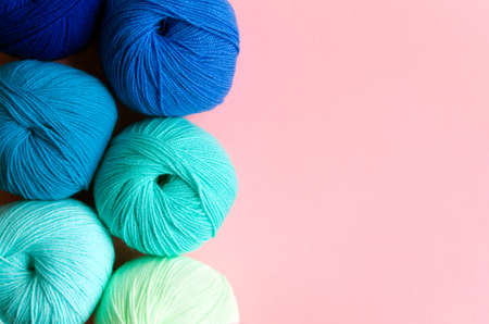 Acrylic balls of yarn in blue-green shades on a pink background. Nuance color combination. Skeins are located vertically on the left.