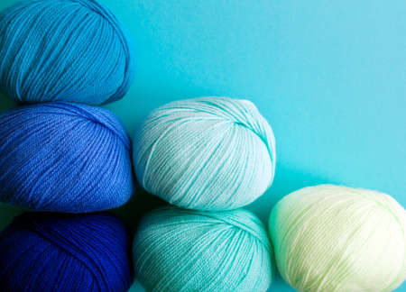 Columnarized acrylic yarn on a light blue background. A graph in the form of a nuanced gradient. The balls of yarn are located diagonally in the lower left corner.