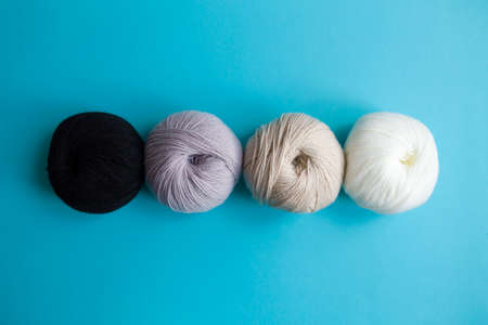 Acrylic balls of yarn on a blue background. Monochrome color combination. The skeins are grouped in one row.