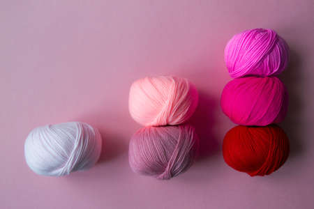 Scoring system in the form of skeins of yarn on a pink background. A graph in the form of a nuanced gradient. Arranged balls of yarn.