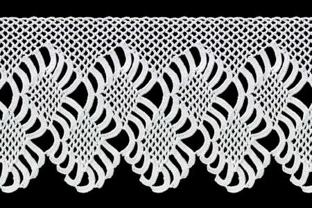 Wide lace tape on a black background. The lace is crocheted by hand. Vintage style. Material for stylish graphic decoration.