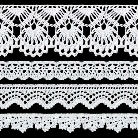Set of white tape lace on a black background. The lace is crocheted by hand. Vintage style. Material for stylish graphic decoration.