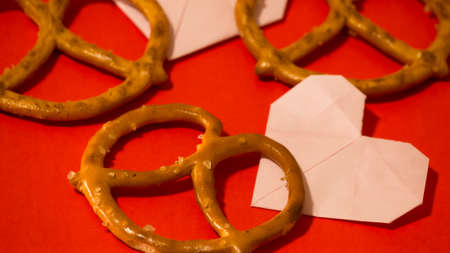 Heart-shaped baked goods pretzels with red background