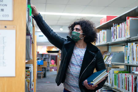 a man who tries to take a book from a bookshelf on a high place