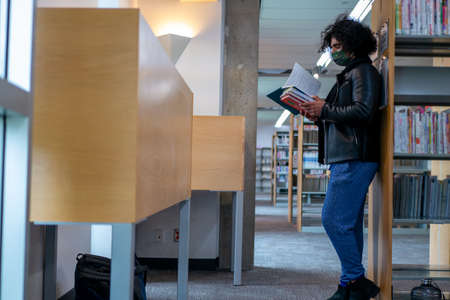 Man standing reading in library