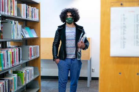 Man walking between bookshelves
