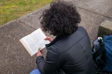 Man sitting on bench reading a book Foto de archivo