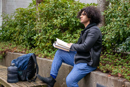 A man and a college student reading a book near a tree Foto de archivo