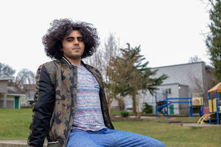 Portrait of man of Middle Eastern background relaxing on outdoor bench
